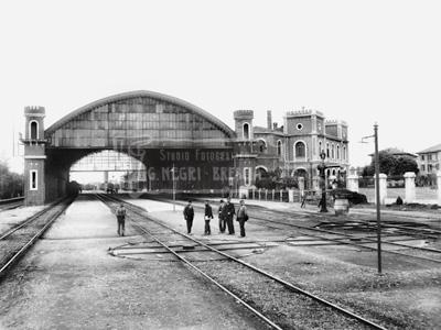 Stazione ferroviaria con copertura e gente sui binari