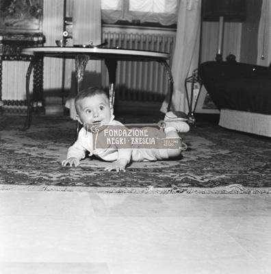 famiglia Orlandi Gigi bambina che gattona sul tappeto del salotto