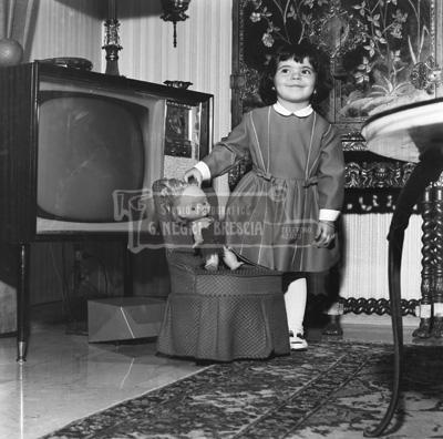 famiglia Orlandi Gigi bambina con bambola in posa nel salotto